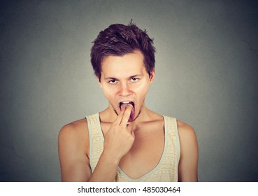 disgusted man with finger in mouth displeased ready to throw up isolated on gray background. Human face expression, emotion