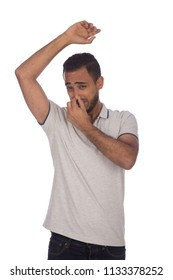 Disgusted man putting his hand over his nose to avoid the bad smell of him, isolated on a white background.