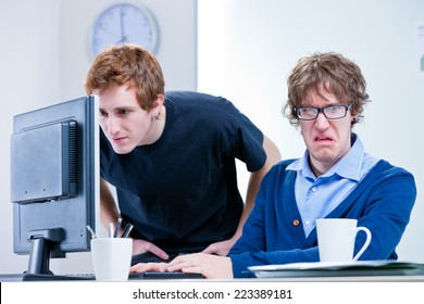 a disgusted office worker while the other one looks for something in a computer screen