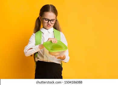 Disgusted Schoolgirl Looking At Sandwich In Lunchbox Over Yellow Studio Background. School Lunch And Gluten Intolerance. Copy Space