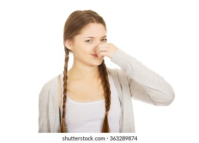 Disgusted teen woman pinching nose.