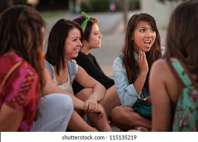 Disgusted teenage girl sitting on the ground talking with friends