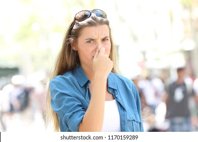 Disgusted woman covering nose in the street of a contaminated city