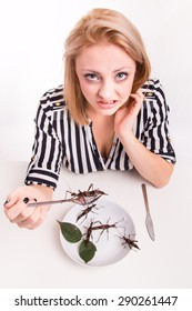 Disgusted woman eating big insects with a fork in a restaurant