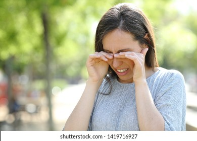 Disgusted woman rubbing her eyes standing outdoors in a park