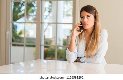 Disgusted woman using smartphone, holding mobile phone, looking at home