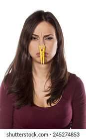 disgusted young woman pinching her nose with a clothespin