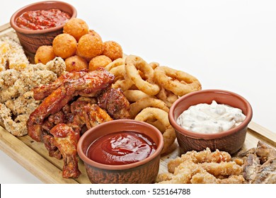 Dish of appetizers to beer. BBQ wings, fried squid rings,  grilled cheese and several different  sauces. Studio shot. Top view.