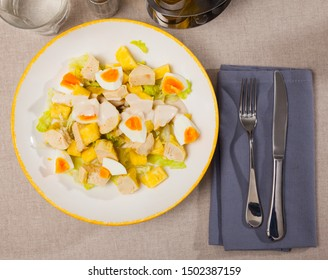 Dish with appetizing chicken salad, eggs and pineapples