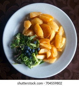 dish with appetizing fried potatoes with salad and blueberries