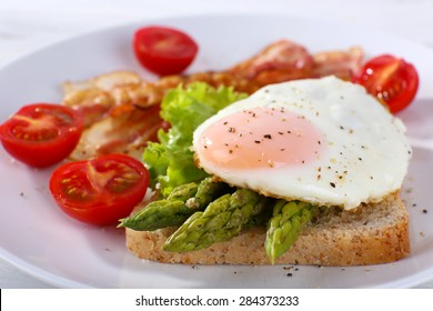 Dish of asparagus and egg in plate on table, closeup