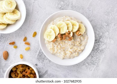 Dish for breakfast. Oats porridge with banana slices and nuts in bowl over stone background. Diet healthy nutrition food concept. Top view, flat lay.