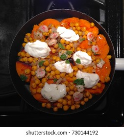 Dish with butternut squash and chickpeas with dollops of yogurt in a pan on the stove, seen from above