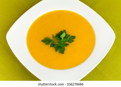 Dish with carrot soup and  garnish parsley.