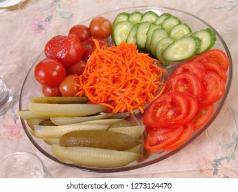Dish with chopped vegetables. Fresh and salty tomatoes. Fresh and salty cucumbers. Grated carrots with hot spices. Cold appetizer for vodka.