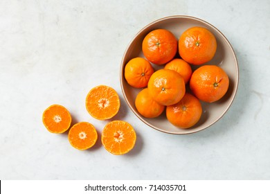 Dish of clementines with sliced clementines on side on white textured background