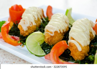 A dish of crispy-fried shrimps with lime sauce.