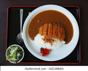 A dish of deep fried pork cutlet topped with Japanese curry side with soup,rice curry and tonkatsu