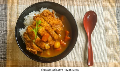 A dish of deep fried pork cutlet topped with Japanese curry side with soup
