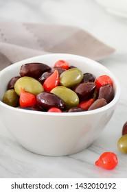 Dish of delicious kalmata olives with mini red peppers in light grey dish on marble background.  Vertical format with focus on center red pepper.