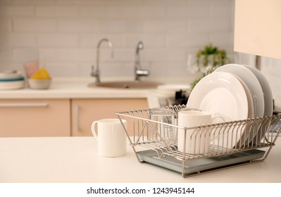 Dish drainer with clean dinnerware on table in kitchen. Space for text