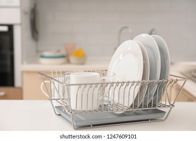 Dish drainer with clean dinnerware on table in kitchen