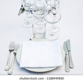 Dish, empty glasses, white napkin, forks and knifes on white tablecloth