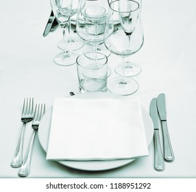 Dish, empty glasses, white napkin, forks and knifes on white tablecloth (green effect)
