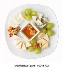 A dish with four kinds of cheese, grapes, walnuts and honey. Top view.