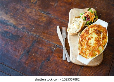 A dish of French cuisine called - Raclette Tartiflette - french kitchen. Meat casserole on a wooden board. Top view with copy space