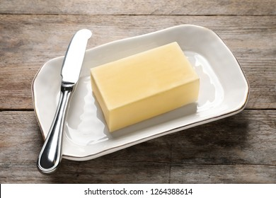Dish with fresh butter and knife on wooden table