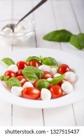 Dish with fresh caprese salad isolated on white