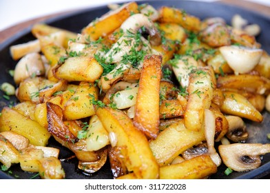 A dish of fried potatoes with mushrooms.