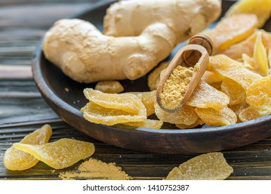 Dish with ginger root, spicy ginger candied fruit and wooden scoop with ground ginger, selective focus.