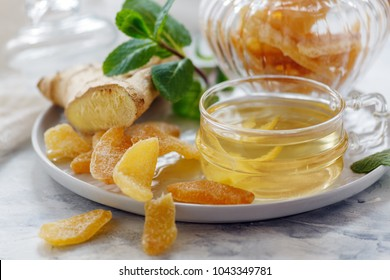 Dish of ginger tea, ginger root and slices of candied ginger on a white kitchen table selective focus.