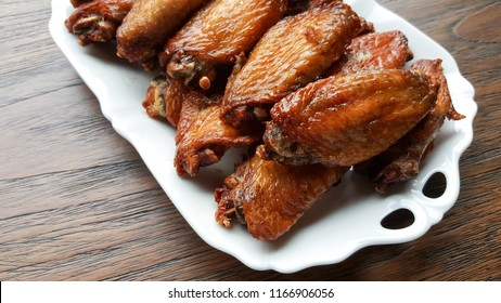 A dish of grilled chicken wings over wooden table background with copy space.
