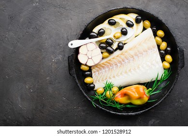 A dish of healthy cuisine with seafood: cod is a white sea fish with lemon slices, olives, sea salt in a cast-iron black frying pan. Top view