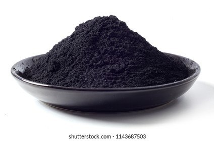 Dish heaped with food grade pulverised black charcoal used as an additive in food and drink for detoxification and cleansing of the body