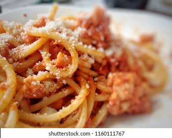 Dish of italian pasta with amatriciana red sauce with grated pecorino cheese on top. Main ingredients are tomatoes and pork cheek. Italy food