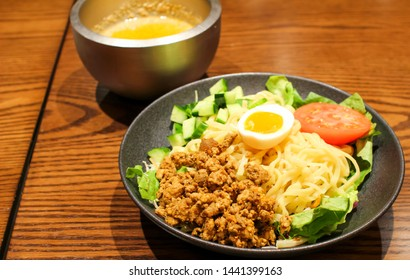Dish in a Japanese restaurant, cold  tantan-men (Dandan noodles) with cucumber, tomatoes, meat and an egg. Sesame sauce in the background.