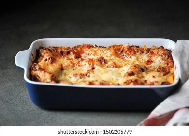 A dish of lasagna. Close-up. Dark background.