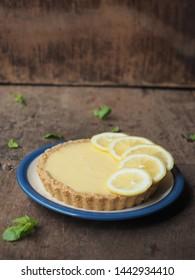 Dish of lemon tart on wooden table.