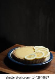 dish of lemon tart on wooden table with dark background