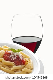 dish with macaroni and tomato sauce and red wine glass