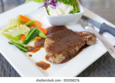 A dish of meat steak covered with herb