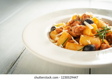 Dish of mezze maniche pasta with sausage, tomato sauce and grated cheese
