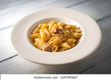 Dish of mezze penne pasta with bacon, pecorino and a pinch of nutmeg