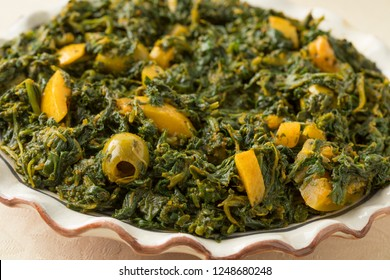 Dish with Moroccan style spinach salad with green olives and preserved lemon close up