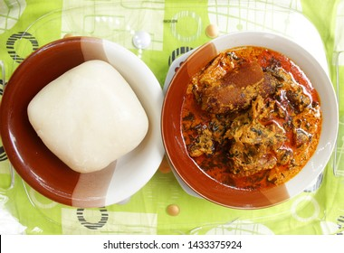 A dish of Nigerian swallow 'Fufu' and 'Egusi Soup' with dried fish, beef and cow skin meat (Kpomo) served in a tray and place on a colorful pattern mint tablecloth (top view)