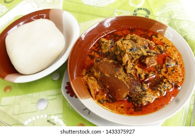 A dish of Nigerian swallow 'Fufu' and 'Egusi Soup' with dried fish, beef and cow skin meat (Kpomo) served in a tray and place on a colorful pattern mint tablecloth